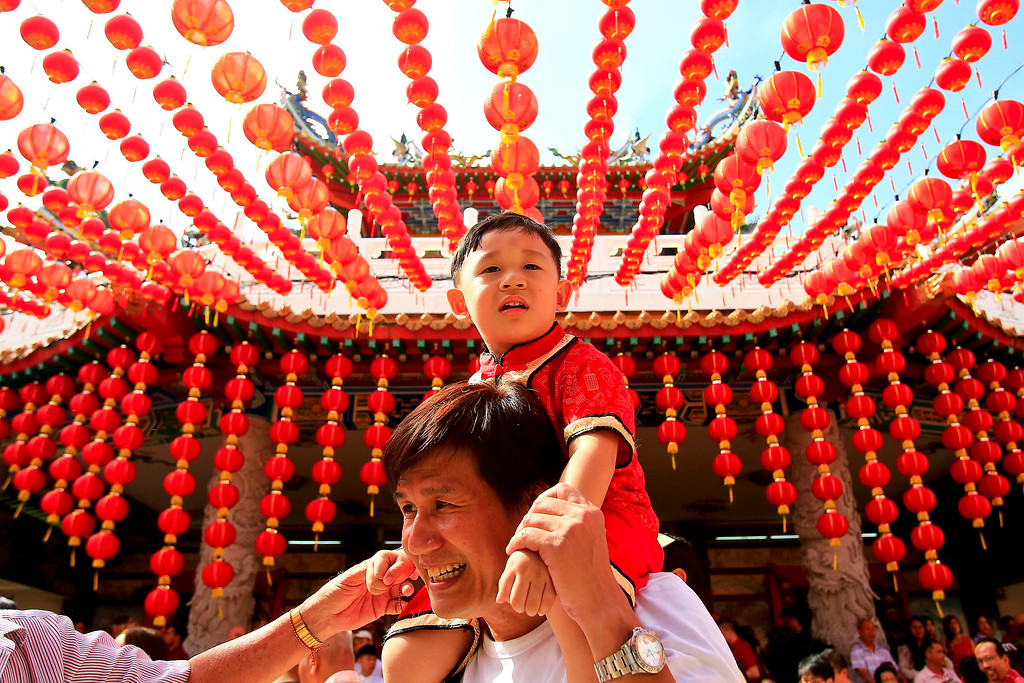 . In this Friday, Feb. 16, 2018, file photo, a man carries his child under traditional Chinese lanterns on the first day of Chinese Lunar New Year at a temple in Kuala Lumpur, Malaysia (AP Photo/Sadiq Asyraf)