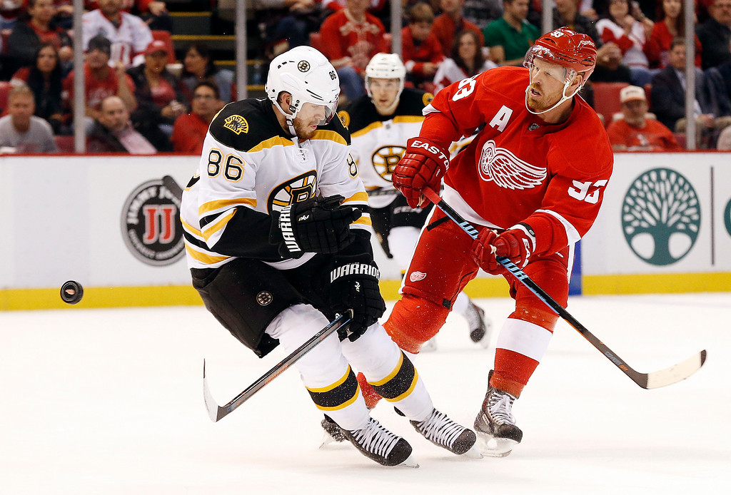 . Detroit Red Wings left wing Johan Franzen (93), of Sweden, shoots past Boston Bruins defenseman Kevan Miller (86) in the second period of a NHL hockey game in Detroit Thursday, Oct. 9, 2014. (AP Photo/Paul Sancya)