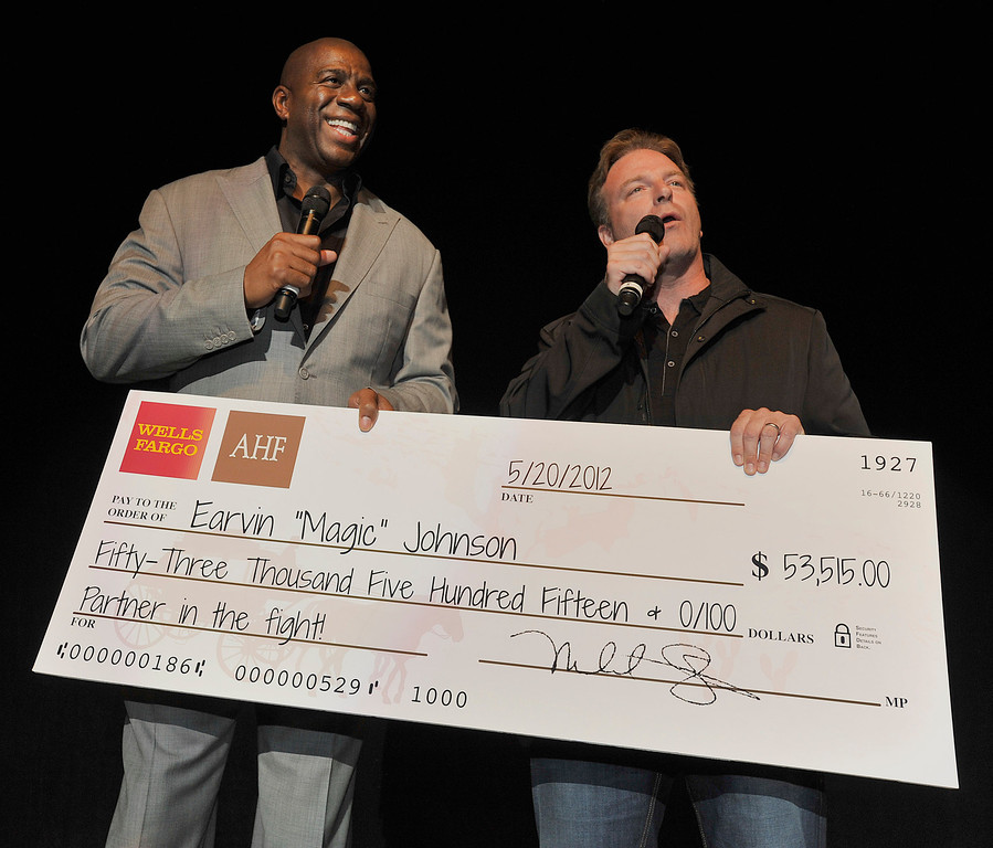 """. In this photograph taken by AP Images for AIDS Healthcare Foundation, Earvin \""""Magic\"""" Johnson, left,  is presented a check by AIDS Healthcare Foundation\'s Vice President Peter Reis on stage for the Magic Johnson Foundation during the California Music Festival AIDS Walk on Sunday May 20, 2012 at The Greek Theatre in Los Angeles. (Eric Reed/AP Images for AIDS Healthcare Foundation)"""