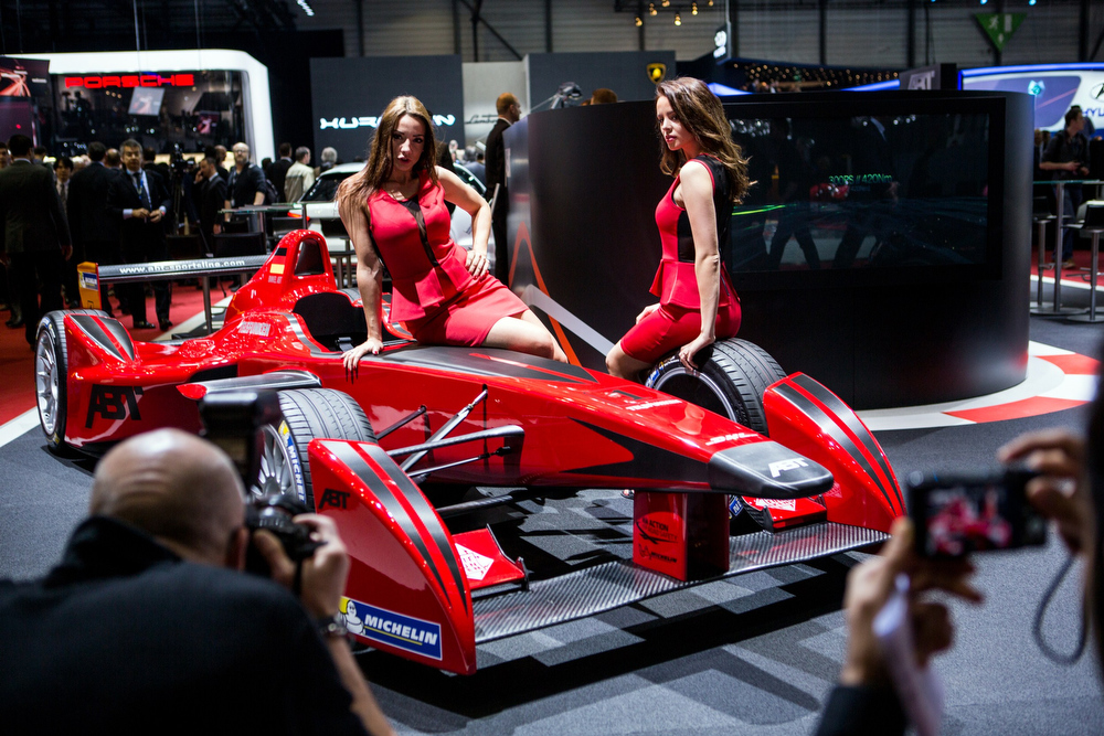 Description of . Hostesses pose on a car at the Abt stand at the Geneva Motor Show in Geneva, Switzerland, on March 4, 2014. AFP PHOTO / PIERRE ALBOUYPIERRE ALBOUY/AFP/Getty Images