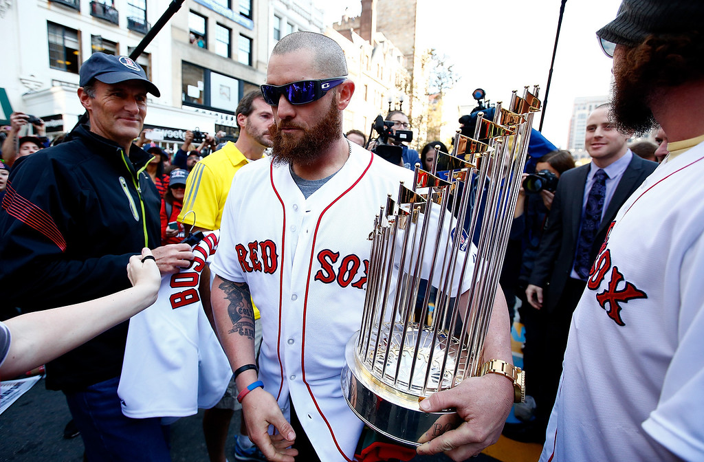 . BOSTON, MA - NOVEMBER 02:  Jonny Gomes #5 carries the World Series trophy near the finish line of the Boston Marathon on Boylston Street during the World Series victory parade on November 2, 2013 in Boston, Massachusetts.  (Photo by Jared Wickerham/Getty Images)