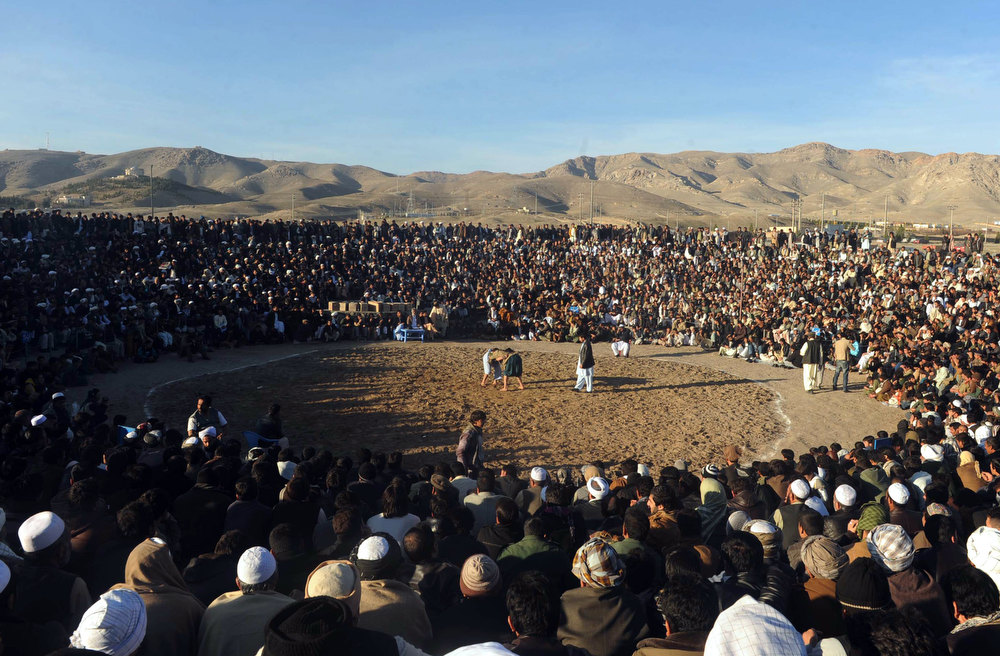 Description of . Spectators watch as Afghan wrestlers compete at an outdoor arena at a field outside Herat on December 21, 2012. Wrestling is a popular sport in the warn-torn nation.  Aref Karimi/AFP/Getty Images