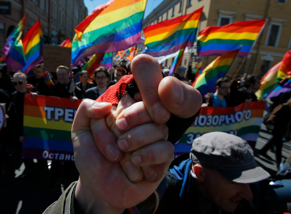 . Gay rights activists clasp hands as they march during a tradition May Day rally in St.Petersburg, Russia, Wednesday, May 1, 2013.  The poster reads : \'We demand the abolition of the homophobic law!\'. (AP Photo/Dmitry Lovetsky)