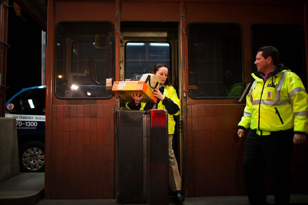 . Toll collector Marilyn Alvardo (C) leaves her tollbooth, as the last human toll collector, at the Golden Gate Bridge toll plaza in San Francisco, California March 27, 2013. The Golden Gate Bridge will convert from manned tollbooths to a full electronic tolling system starting today. With the automated system in place, motorists will have the option of using the existing FasTrak electronic toll collection system or the newly implemented pay-by-plate option, according to the Golden Gate Bridge management. REUTERS/Stephen Lam