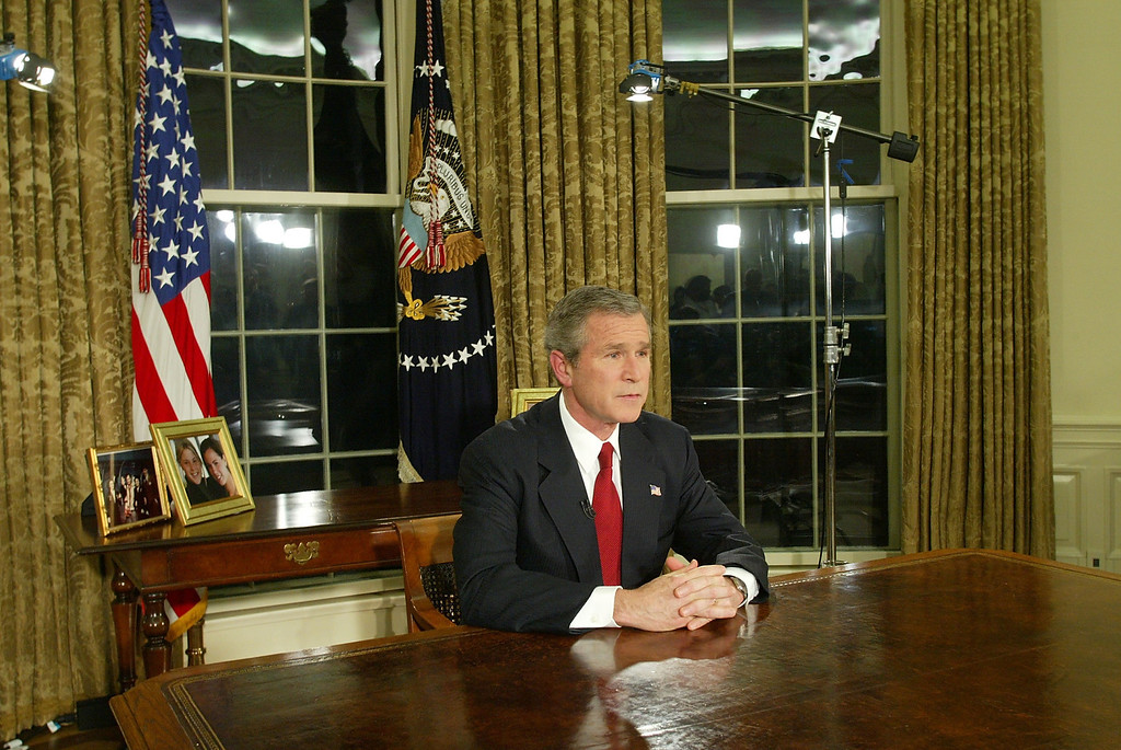 """. U.S. President George W. Bush addresses the nation March 19, 2003 in the Oval Office of the White House in Washington, DC. Bush announced that the U.S. military struck at \""""targets of opportunity\"""" in Iraq. Air defense sirens and anti-aircraft fire was reported briefly in Baghdad. (Photo by Alex Wong/Getty Images)"""