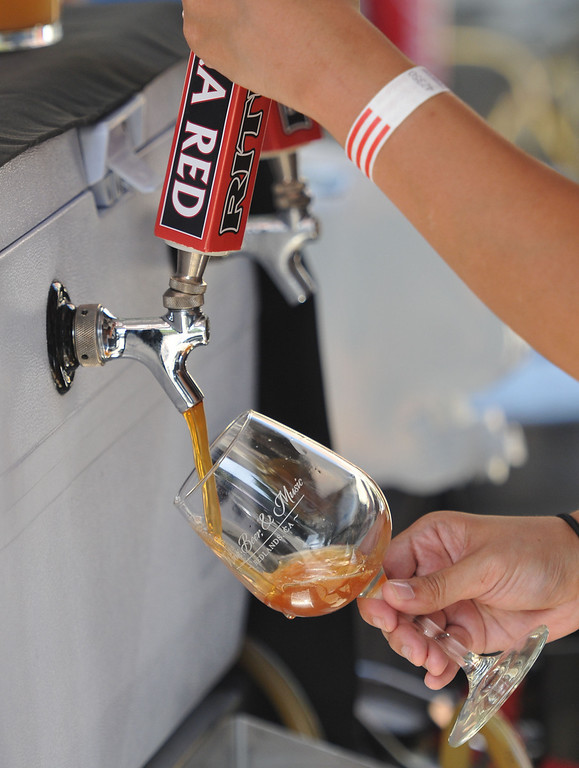 . (John Valenzuela/Staff Photographer)  Adrienne Macalinao of Ritual Brewery, pours a glass of their Extra Red Ale during the Redlands Wine, Beer, and Music event at Ed Hales Park in downtown Redlands, Saturday, June 22, 2013.