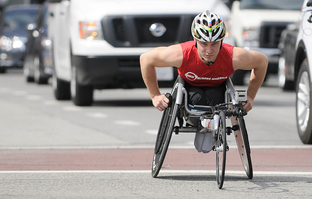 """. Ryan Chalmers wheels down Main Street in Los Angeles. Chalmers is pushing himself in a wheel chair on a coast-to-coast trip that starts at the JW Marriott in Los Angeles, and will end in New York\'s Central Park. The 3000 mile odysey will raise funds for an organization called  \""""Stay Focused\"""" that allows teens and young adults with disabilities to participate in sports alongsid able-bodied people.  Los Angeles CA 4/6/2013(John McCoy/Staff Photographer"""