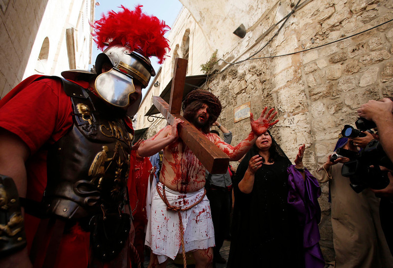 . A man playing the role of Jesus carries a cross to the Church of the Holy Sepulchre on Good Friday during Holy Week, in Jerusalem\'s Old City March 29, 2013. Christian worshippers retraced the route Jesus took along Via Dolorosa to his crucifixion in the Church of the Holy Sepulchre. Holy Week is celebrated in many Christian traditions during the week before Easter. REUTERS/Baz Ratner