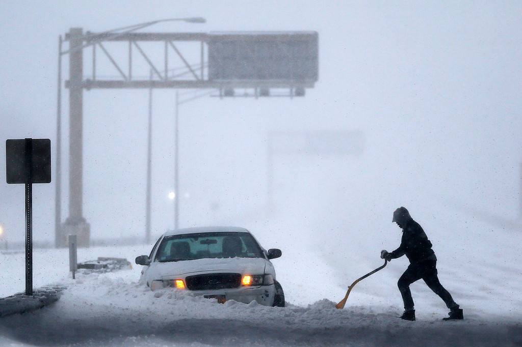 . A motorist shovels snow to free up a vehicle on the New Jersey Turnpike during a snowstorm, Saturday, Jan. 23, 2016, in Port Reading, N.J. Towns across the state are hunkering down during a major snowstorm that hit overnight. (AP Photo/Julio Cortez)