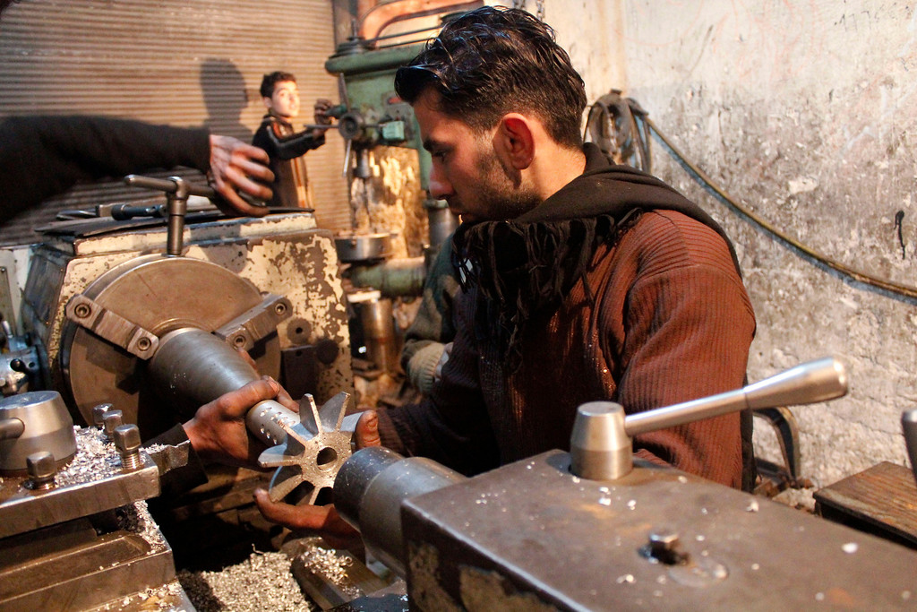 . A man works on an improvised mortar shell for the Free Syrian Army inside a factory which previously manufactured steel and iron in Aleppo February 18, 2013. REUTERS/Hamid Khatib