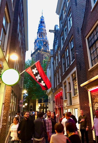 """Old Church"" looming above the streets of the Red Light District. The red lights above the doorways indicate a woman is offering services."