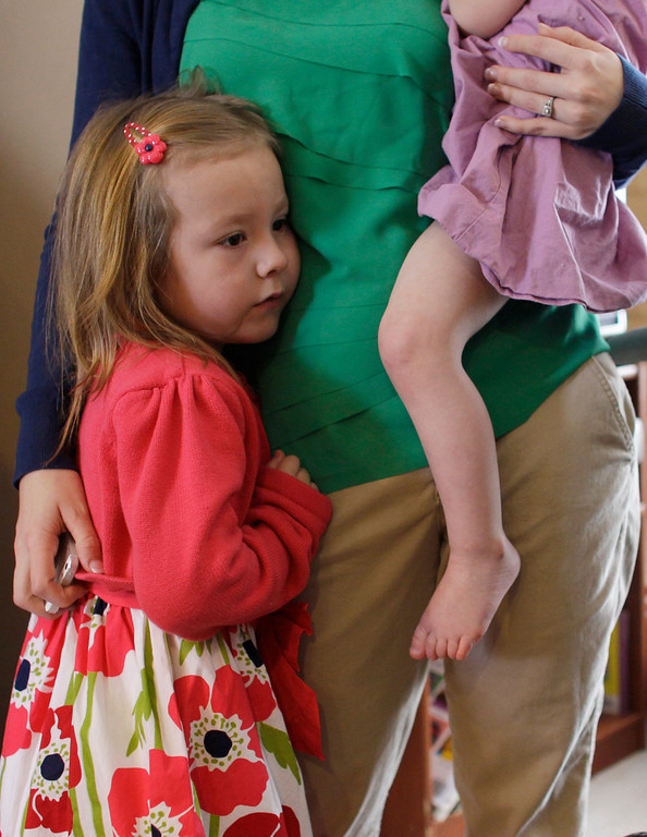 . In this Monday, Feb. 25, 2013, photo, Coy Mathis hugs her mother Kathryn, who holds Coy\'s sister Auri, at their home in Fountain, Colo.  (AP Photo/Brennan Linsley)