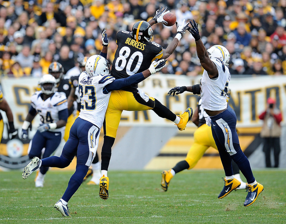 . Plaxico Burress #80 of the Pittsburgh Steelers makes a catch between the defense of Quentin Jammer #23 and Takeo Spikes #51 of the San Diego Chargers on December 9, 2012 at Heinz Field in Pittsburgh, Pennsylvania.  (Photo by Joe Sargent/Getty Images)