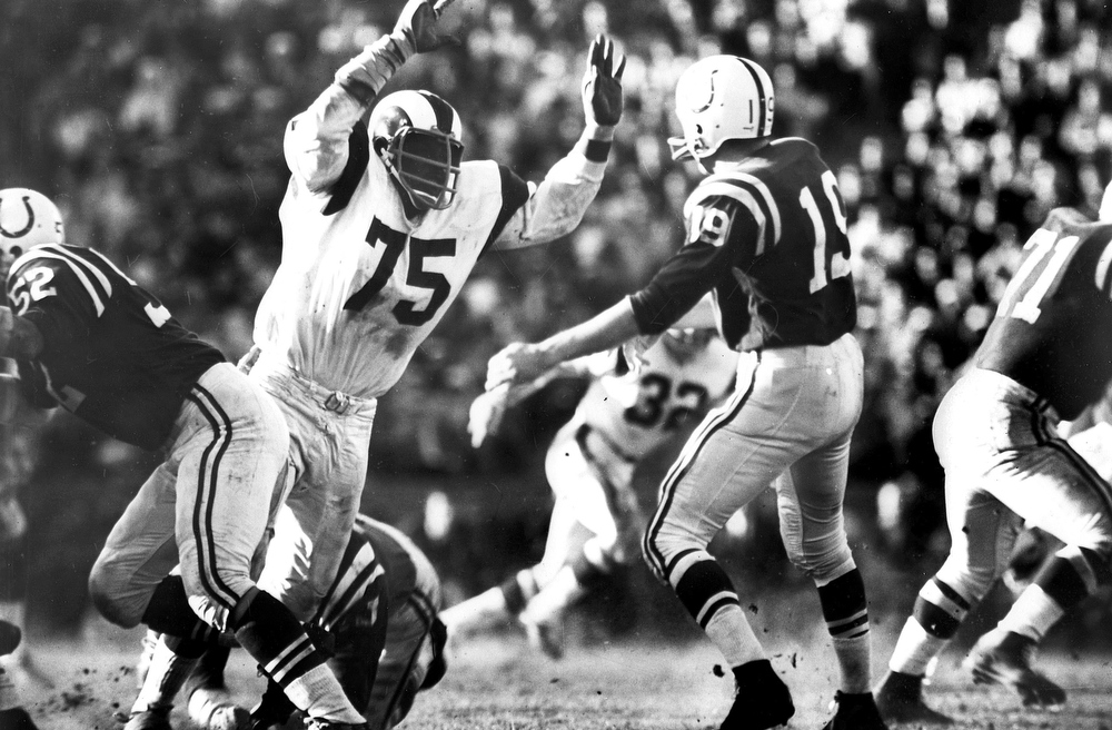 """. In this Dec. 15, 1968 photo provided by NFL Photos, Hall of Fame defensive end David \""""Deacon\"""" Jones (75) of the Los Angeles Rams rushes Baltimore Colts Hall of Fame quarterback Johnny Unitas (19) in Los Angeles. (AP Photo/NFL Photos)"""