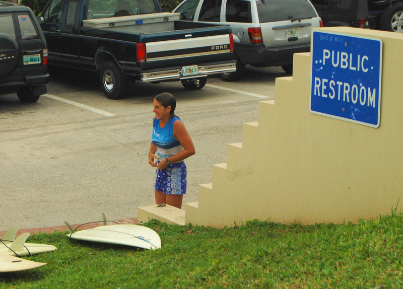 Young surfer girl preparing to leave after a morning of riding the waves near Ormond Beach, FL