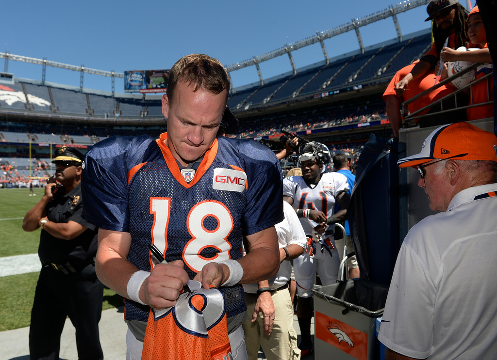 . Denver Broncos QB, Peyton Manning, signs a jersey for a fan after practice and scrimmage at Sports Authority Field at Mile High Saturday afternoon, August 02, 2014. (Photo By Andy Cross / The Denver Post)