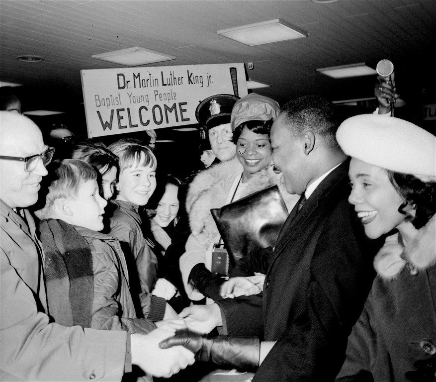 . American integrationist leader Dr. Martin Luther King, Jr., is welcomed by Baptist youths on arrival in Oslo, Norway, December 8, 1964.  Dr. King is flanked by his wife, Coretta, right, and his secretary, Miss Dora McDonald.  Dr. King is in the Norwegian capital to accept a 1964 Nobel Peace Prize to be presented to him during ceremonies December 10.  (AP Photo)
