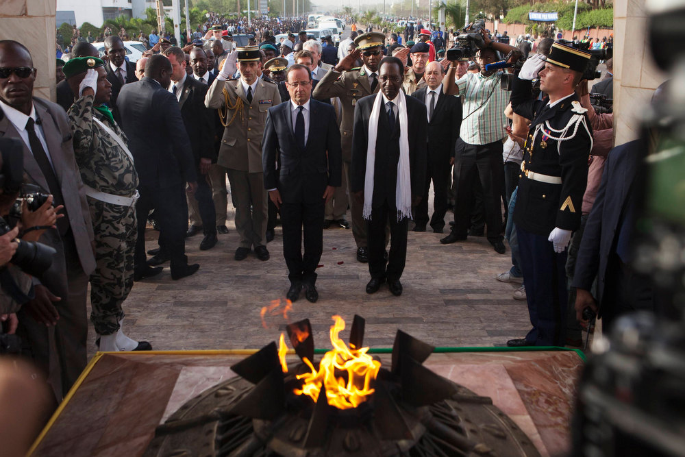Description of . France\'s President Francois Hollande (L) stands with Mali\'s interim president Dioncounda Traore before placing flowers in homage to deceased Malian soldiers at the Independence Plaza in Bamako, Mali February 2, 2013. France will withdraw its troops from Mali once the Sahel state has restored sovereignty over its national territory and a U.N.-backed African military force can take over from the French soldiers, Hollande said on Saturday. REUTERS/Joe Penney