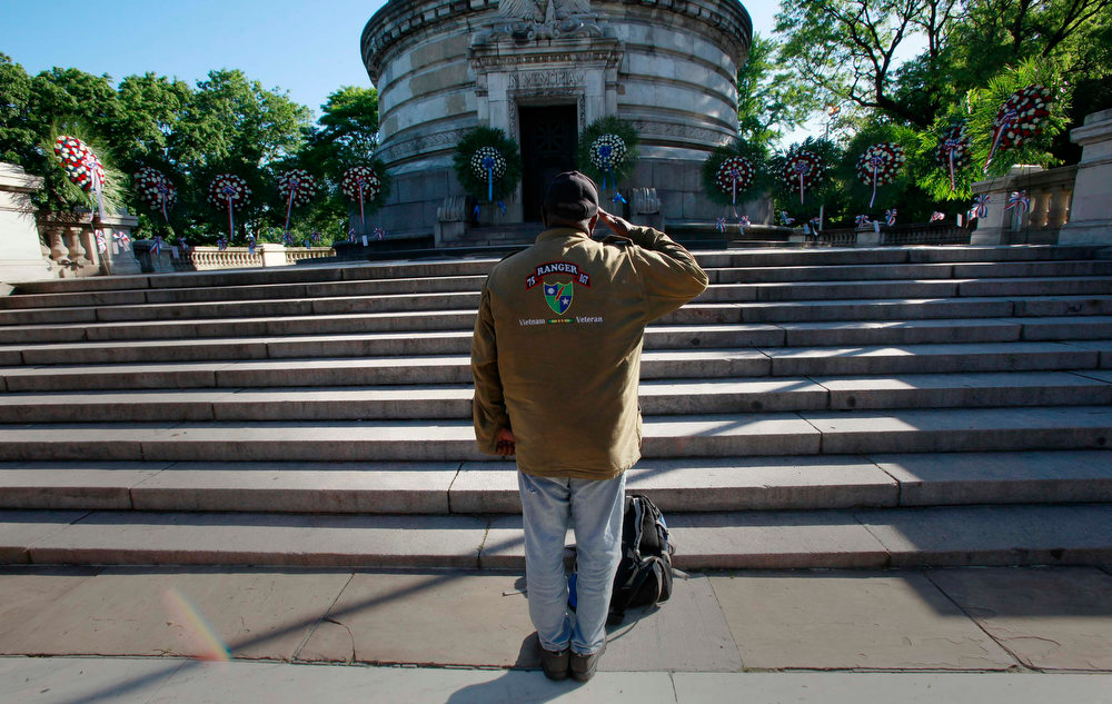 . An unidentified veteran salutes while looking at wreathes laid at the Soldiers and Sailors Monument hours before the beginning of a Memorial Day service on the Upper West Side of New York, May 27, 2013.    REUTERS/Carlo Allegri