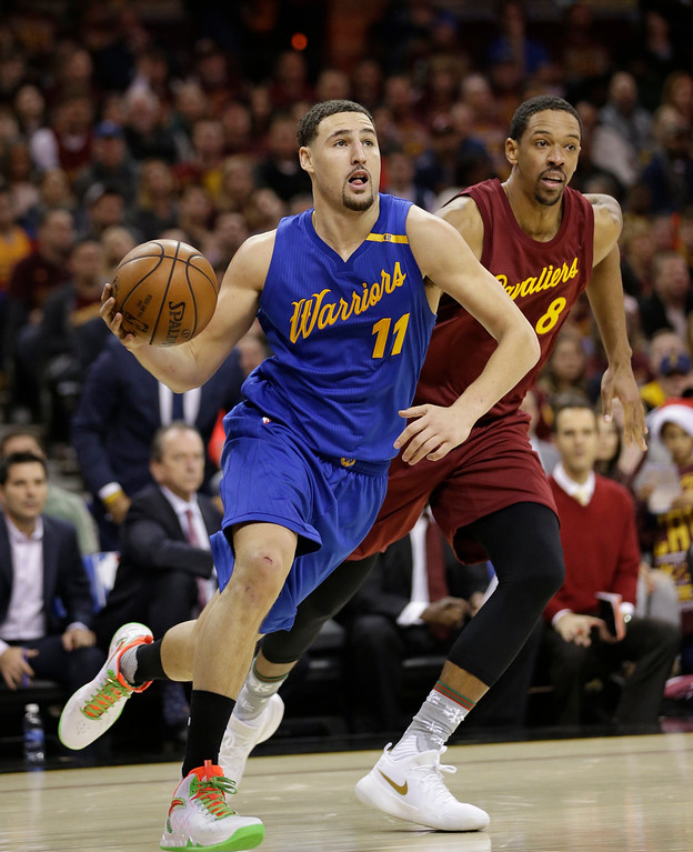 . Golden State Warriors\' Klay Thompson (11) drives past Cleveland Cavaliers\' Channing Frye (8) in the second half of an NBA basketball game, Sunday, Dec. 25, 2016, in Cleveland. (AP Photo/Tony Dejak)