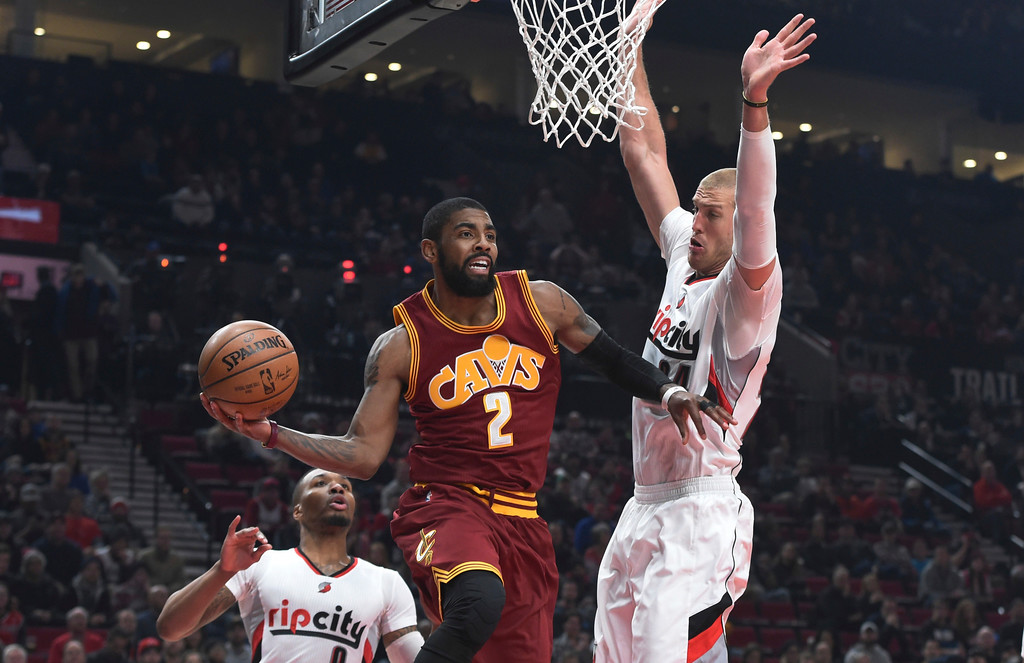 . Cleveland Cavaliers guard Kyrie Irving passes the ball as Portland Trail Blazers center Mason Plumlee defends during the first half of an NBA basketball game in Portland, Ore., Wednesday, Jan, 11, 2017. (AP Photo/Steve Dykes)