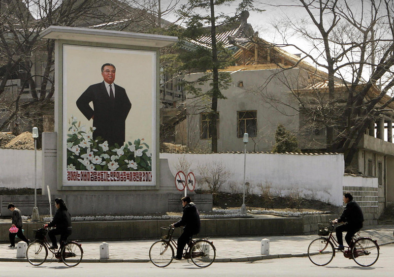 """. North Koreans ride past a poster of the late leader Kim Il-Sung in the town of Kaesong, near the Demilitarized Zone at Panmanjon in North Korea, 27 March 2005.  Kim Il-Sung ruled North Korea from the nation\'s founding in 1948 until his death in 1994. His son, Kim Jong-Il, succeeded him in power although he remains \""""president for life\"""", as enshrined in the constitution, and his image still appears everywhere around the country.  (PETER PARKS/AFP/Getty Images)"""