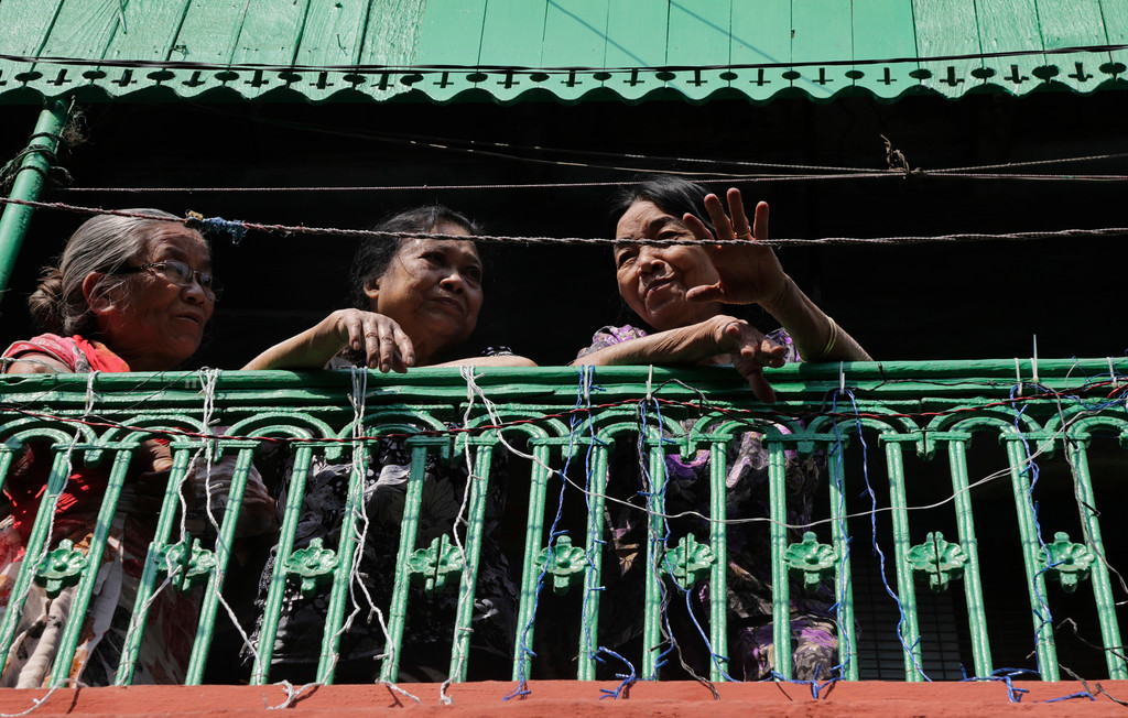 . Ethnic Chinese women from a balcony watch a procession of lion dancers on the first day of Lunar New Year in Kolkata, India, Friday, Feb. 16, 2018. People in Asia and around the world are celebrating the Lunar New Year on Friday with festivals, parades and temple visits to ask for blessings. This year marks the year of the dog, one of the 12 animals in the Chinese astrological chart. (AP Photo/Bikas Das)
