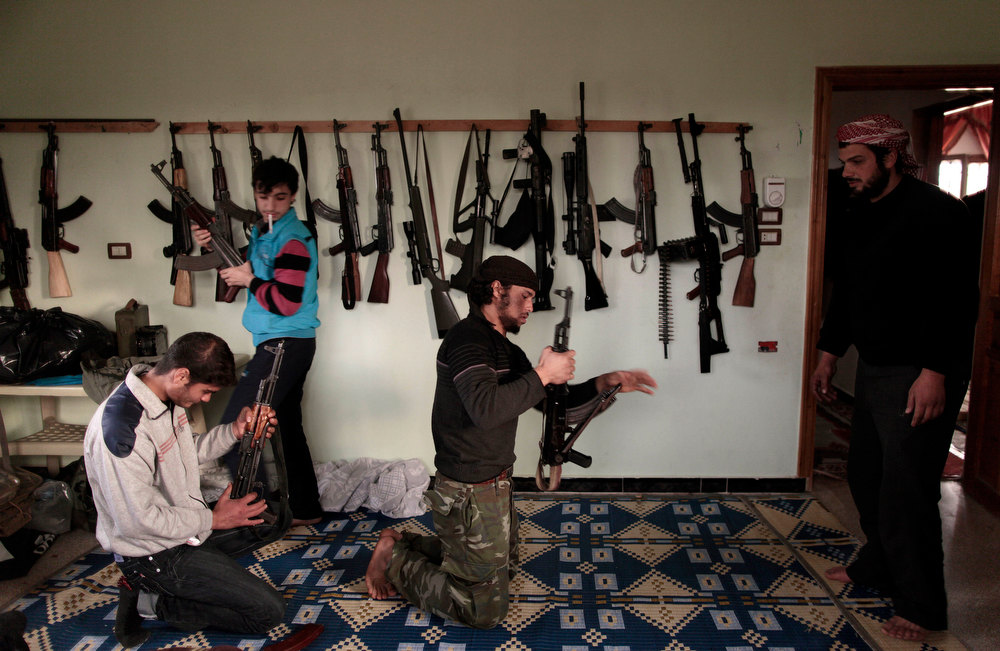 Description of . Syrian rebels clean their weapons at their headquarters in Maaret Misreen, near Idlib, Syria, Wednesday, Dec. 12, 2012. (AP Photo/Muhammed Muheisen)