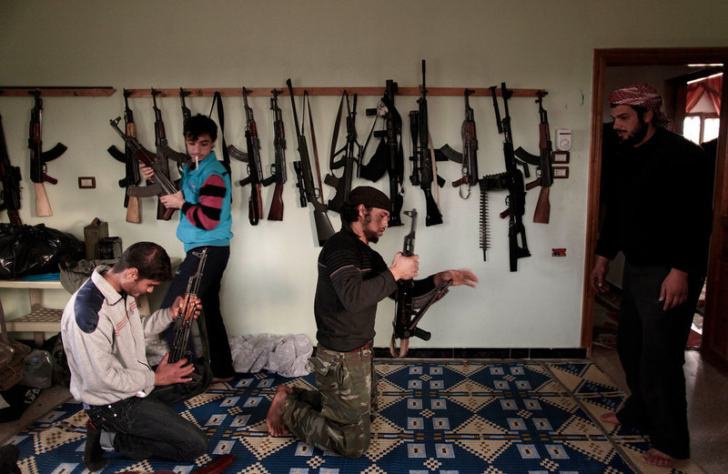 . Syrian rebels clean their weapons at their headquarters in Maaret Misreen, near Idlib, Syria, Wednesday, Dec. 12, 2012. (AP Photo/Muhammed Muheisen)