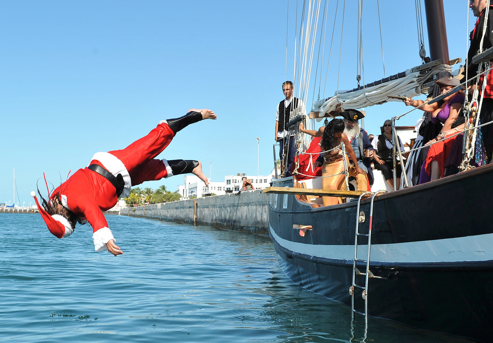 Description of . In this photo released by the Florida Keys News Bureau, Klaus Chroszielewski, dressed as Santa Claus, competes in the National Walk the Plank contest Saturday, Dec. 3, 2011, in Key West, Fla. The Baltimore resident defended his 2010 title in the competition that was a facet of Key West's annual Pirates in Paradise festival that ends Sunday. Contestants were judged on their pleas, costuming, plank-walking style and splash. (AP Photo/Florida Keys News Bureau, Bert Budde)