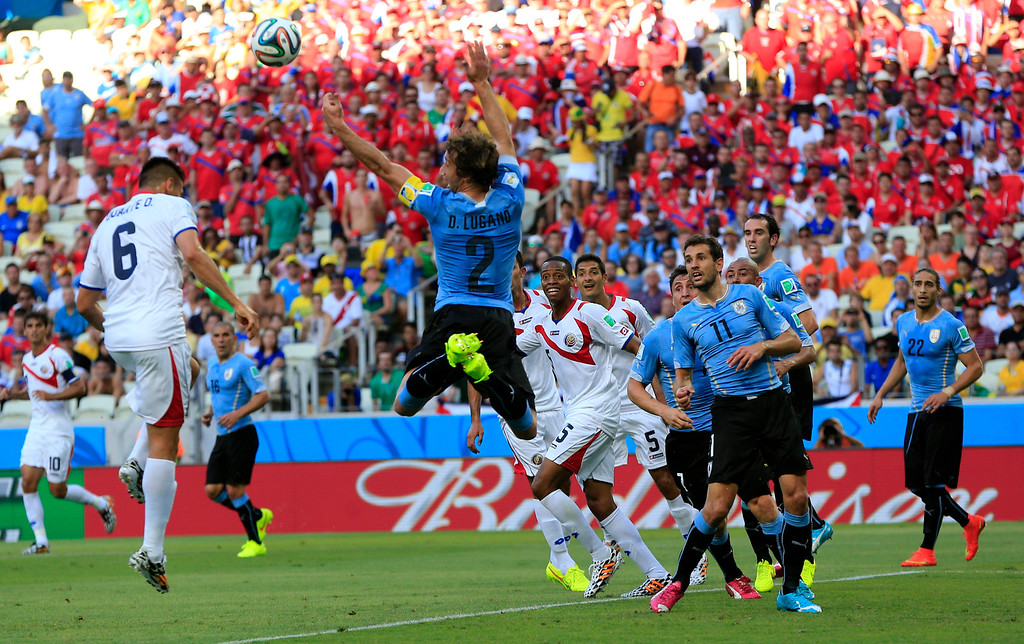 . Costa Rica\'s Oscar Duarte, left, takes a header but is penalized for pushing Uruguay\'s Diego Lugano, center, during the group D World Cup soccer match between Uruguay and Costa Rica at the Arena Castelao in Fortaleza, Brazil, Saturday, June 14, 2014.  (AP Photo/Bernat Armangue)