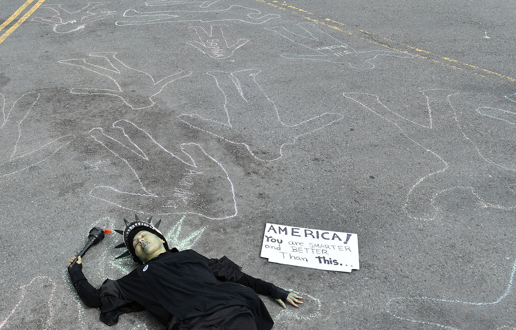 ". Dressed as lady liberty, Rosa Plume lies on the street as crowds of people participate in the ""March for Our Lives\"" rally in support of gun control, Saturday, March 24, 2018, in San Francisco. In a historic groundswell of youth activism, hundreds of thousands of teenagers and their supporters rallied across the U.S. against gun violence Saturday, vowing to transform fear and grief into a \""vote-them-out\"" movement and tougher laws against weapons and ammo. (AP Photo/Josh Edelson)"