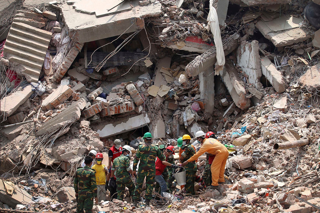 . Workers try to release two bodies trapped in the rubble of collapsed Rana Plaza garment factory building in Savar, near Dhaka, Bangladesh, April 30, 2013. The collapse of Rana Plaza in Dhaka that killed 1,129 people.  (AP Photo/Wong Maye-E, File)
