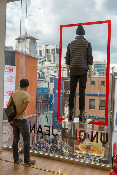 Man standing in store, looking through glass window, Seoul, South Korea