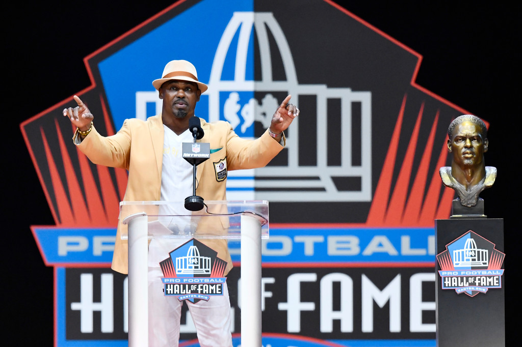 . Former NFL player Brian Dawkins delivers a speech beside during an induction ceremony at the Pro Football Hall of Fame, Saturday, Aug. 4, 2018, in Canton, Ohio. (AP Photo/David Richard)