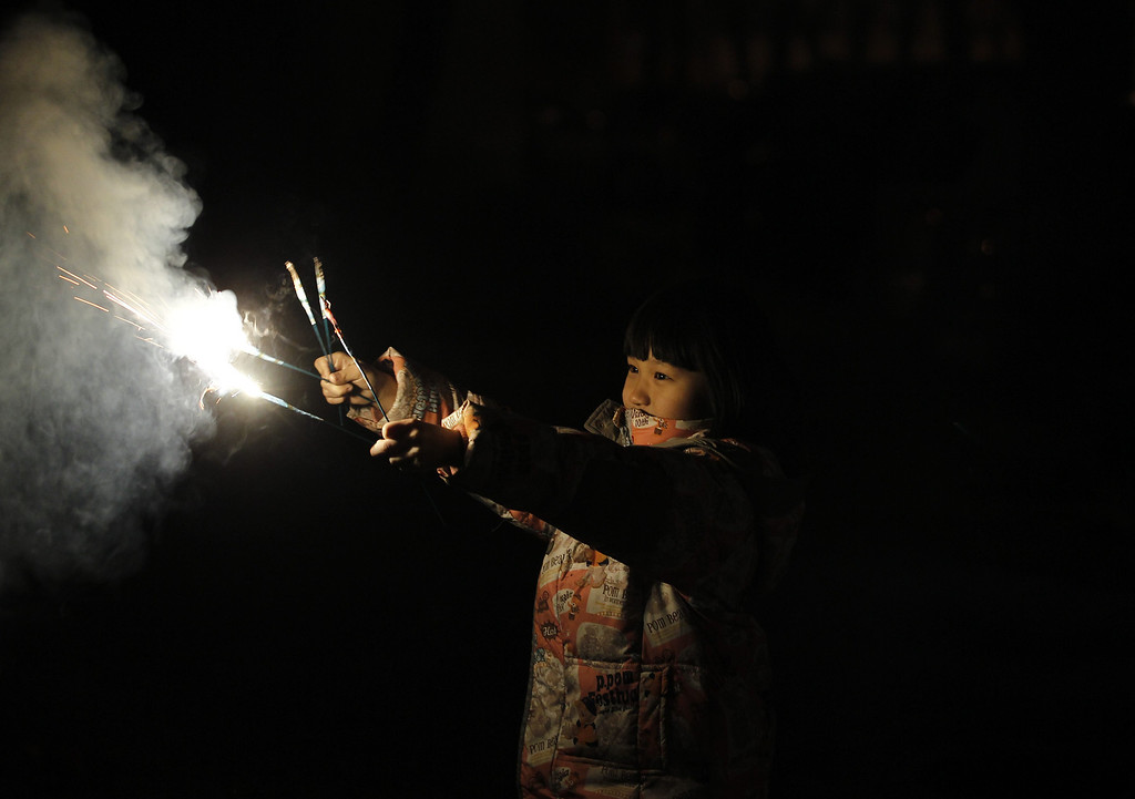 . A child holds sparklers outside her home minutes after midnight in Beijing, China, 31 January 2014. The Lunar New Year ushers in the Year of the Horse on 31 January, and officially starts the Spring Festival in China.  EPA/ROLEX DELA PENA