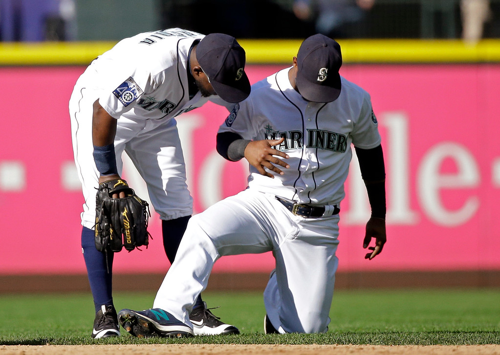 . Seattle Mariners shortstop Jean Segura, right, gets support from center fielder Guillermo Heredia after injuring his right hand in the ninth inning of a baseball game against the Cleveland Indians  Saturday, Sept. 23, 2017, in Seattle. (AP Photo/Elaine Thompson)