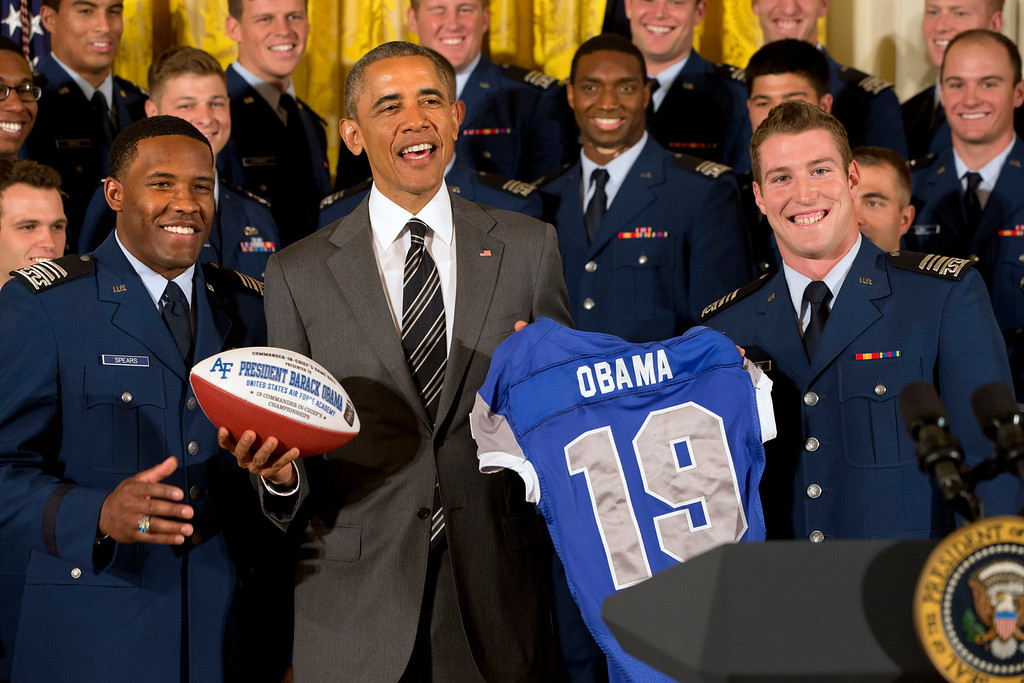 . Air Force defensive back Christian Spears, left, and quarterback Kale Pearson, right, smile after handing President Barack Obama a football and jersey during an event in the East Room of the White House in Washington, Thursday, May 7, 2015, where the president honored the U.S. Air Force Academy football team with the Commander-in-Chief Trophy. (AP Photo/Jacquelyn Martin)