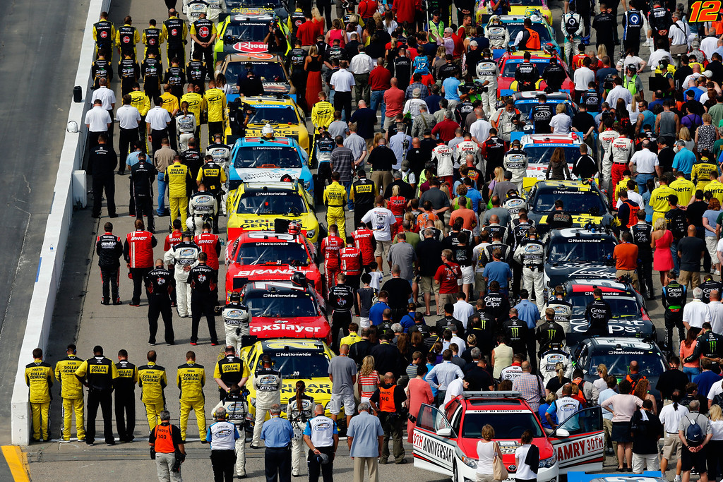 . LOUDON, NH - JULY 13:  Drivers and crew members stand on the grid during the national anthem prior to the NASCAR Nationwide Series CNBC Prime\'s The Profit 200 at New Hampshire Motor Speedway on July 13, 2013 in Loudon, New Hampshire.  (Photo by Jared Wickerham/Getty Images)