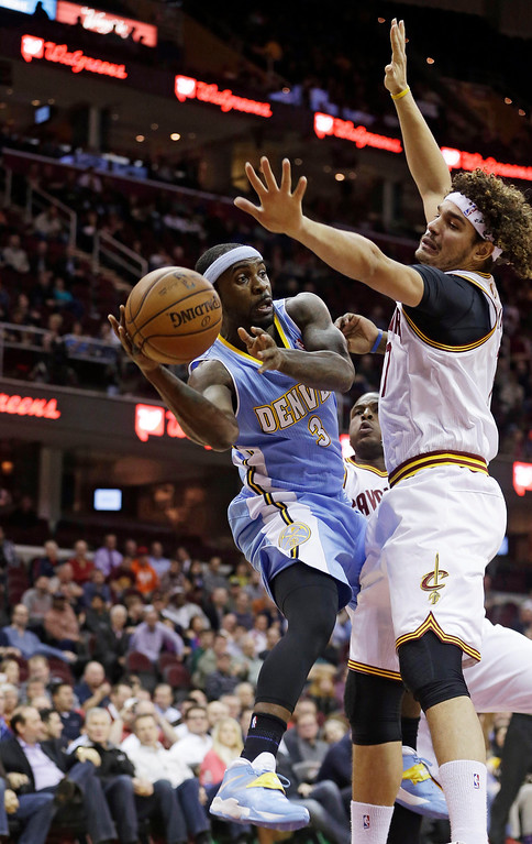 . Denver Nuggets\' Ty Lawson (3) passes the ball around Cleveland Cavaliers\' Anderson Varejao (17), from Brazil, during the first quarter of an NBA basketball game on Wednesday, Dec. 4, 2013, in Cleveland. (AP Photo/Tony Dejak)