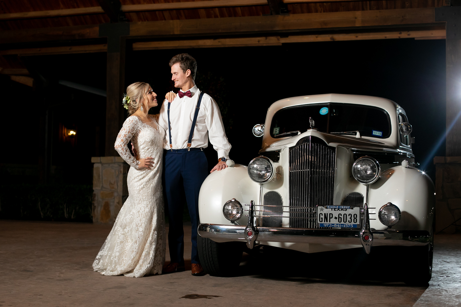 a newlywed couple standing next to a classic white car