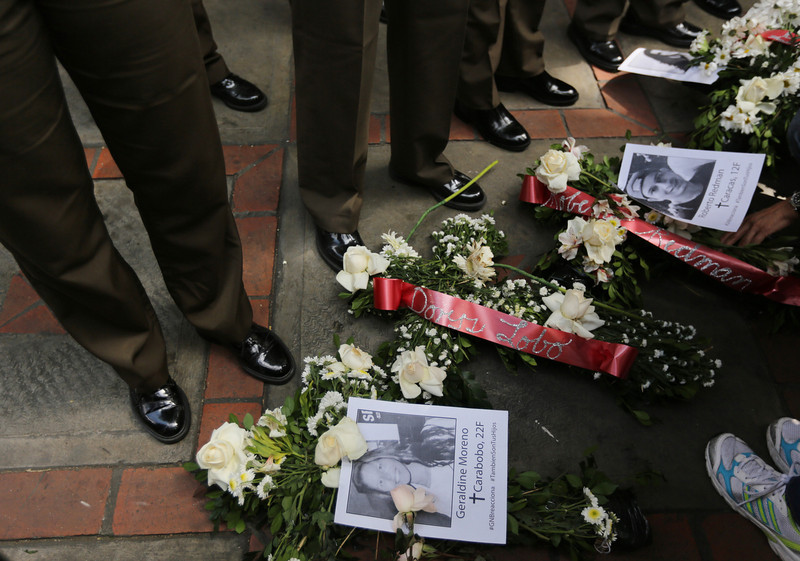 . Flowers with images of slain students Geraldine Moreno, bottom, and Roberto Redman, top, lay at the feet Bolivarian National Guard officers outside their headquarters where a women\'s march arrived to protest repression against anti-government demonstrators in Caracas, Venezuela, Wednesday, Feb. 26, 2014. Moreno was near her home in Valencia watching students defend a barricade at the corner of her street when national guardsmen rushed in and fired rubber bullets at close range, hitting her in the face. She died from brain injuries on Saturday. Redman was shot and killed in a standoff with police on Feb. 12 in Caracas at the end of an opposition protest. (AP Photo/Fernando Llano)