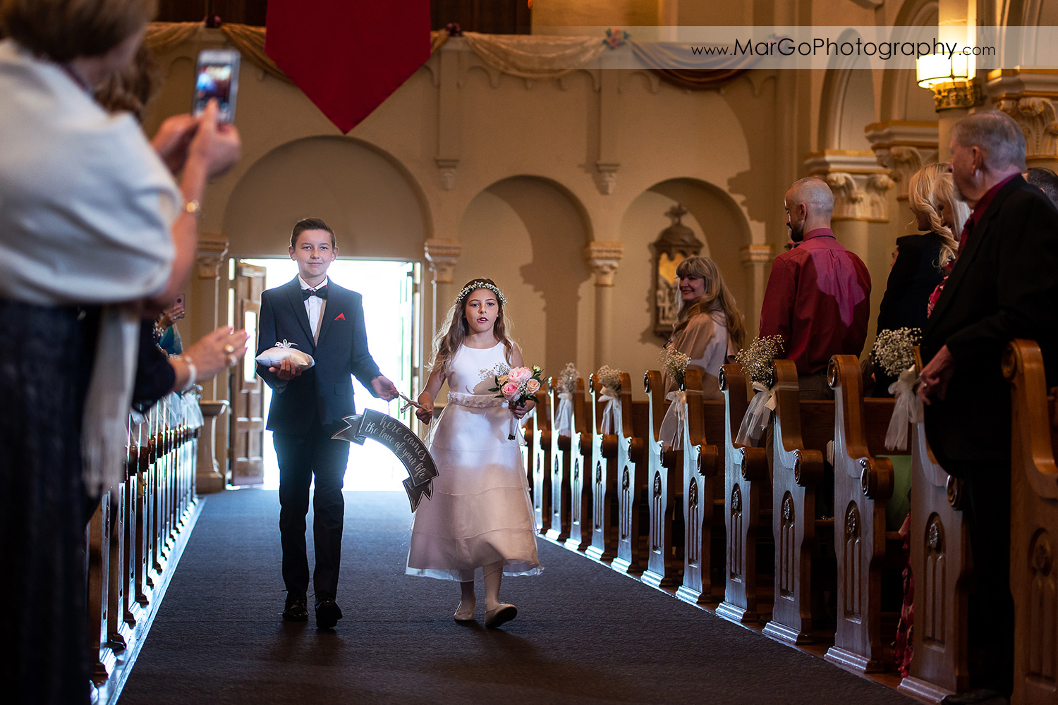 flower girl and ring bearer walking down the aisle during wedding ceremony at Oakland Church of Saint Leo the Great