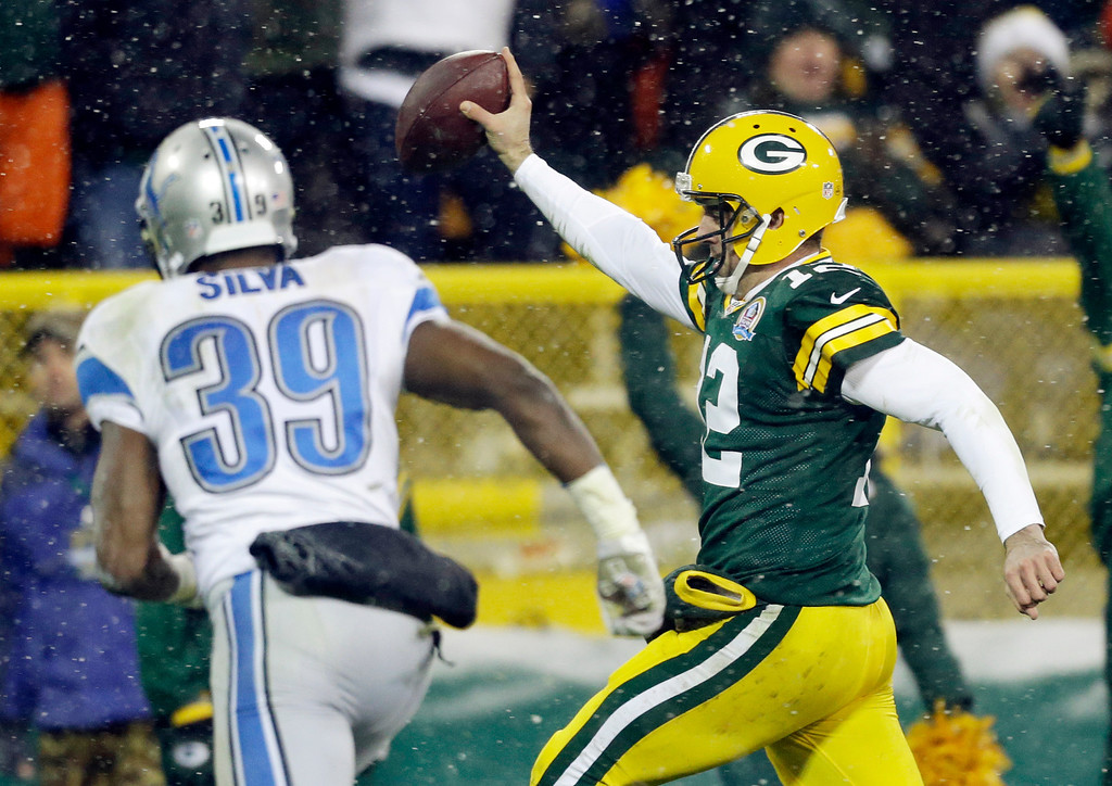. Green Bay Packers quarterback Aaron Rodgers breaks away from Detroit Lions\' Ricardo Silva (39) for a 27-yard touchdown run during the second half of an NFL football game Sunday, Dec. 9, 2012, in Green Bay, Wis. (AP Photo/Jeffrey Phelps)