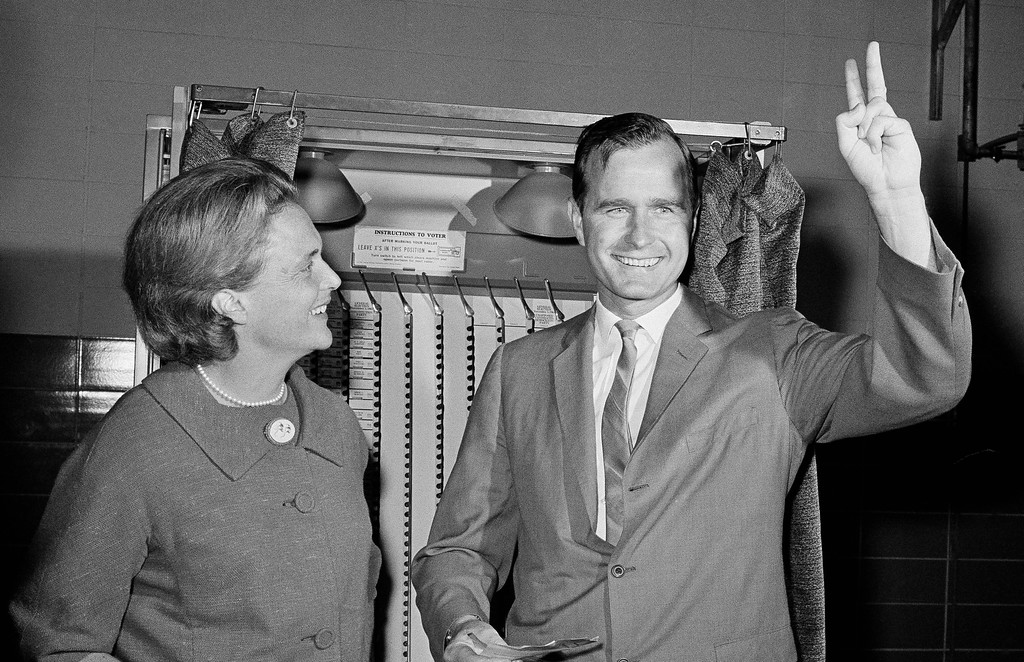 . Republican Senatorial candidate George Bush shows a victory sign as he and his wife Barbara stand in front of a vote machine November 3, 1964 in Houston,Tex., just before casting their ballot.   The candidate waited an hour and a half in a long of votes that circled the Pilgrim Elementary School where the Bush\'s voted this morning. in Houston.    (AP Photo).