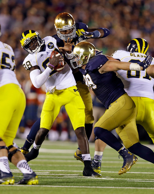 . Michigan quarterback Devin Gardner, left, is pressured by Notre Dame defensive lineman Andrew Trumbetti, right, and Jarron Jones during the second half of an NCAA college football game in South Bend, Ind., Saturday, Sept. 6, 2014. (AP Photo/Michael Conroy)