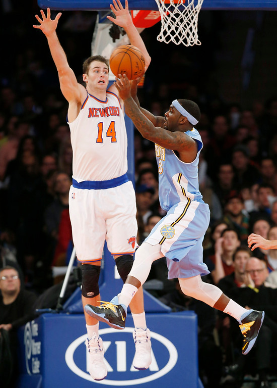 . Denver Nuggets guard Ty Lawson (3) passes as New York Knicks center Jason Smith (14) defends in the second half of an NBA basketball game at Madison Square Garden in New York, Sunday, Nov. 16, 2014. The Knicks defeated the Nuggets 109-93. (AP Photo/Kathy Willens)