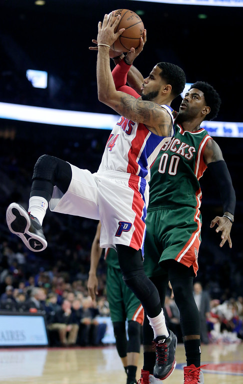 . Milwaukee Bucks\' O.J. Mayo (00) tries to defend against a shot by Detroit Pistons\' D.J. Augustin (14) during the second half of an NBA basketball game Friday, Nov. 7, 2014, in Auburn Hills, Mich. The Pistons defeated the Bucks 98-95. (AP Photo/Duane Burleson)
