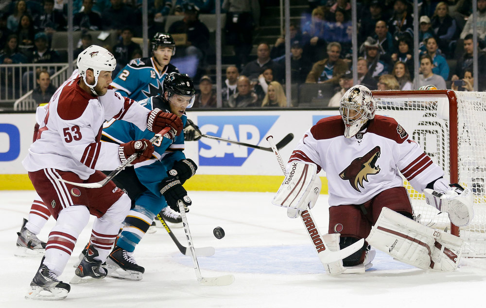 Description of . From left, Phoenix Coyotes defenseman Derek Morris (53) defends on San Jose Sharks center Joe Pavelski, center, as goalie Jason LaBarbera watches during the first period of an NHL hockey game in San Jose, Calif., Thursday, Jan. 24, 2013. (AP Photo/Marcio Jose Sanchez)