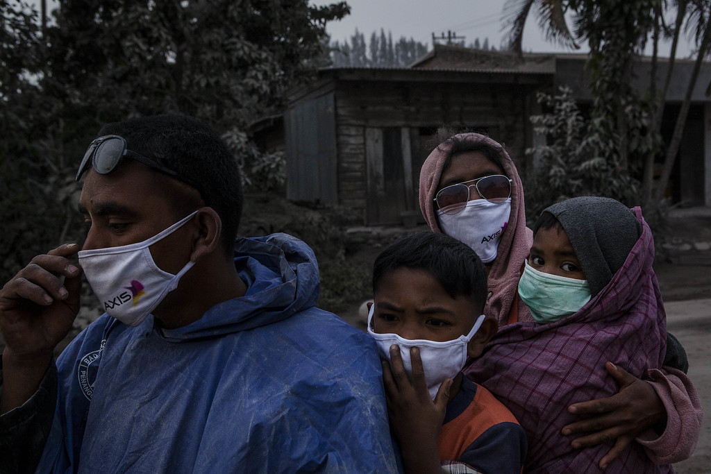 . A family cover their face as passing through an area covered by ash after Mount Sinabung erupted spewing volcanic materials on October 13, 2014 in Berastagi, Karo district, North Sumatra, Indonesia. Mount Sinabung, which had lain dormant for over 400 years, has been intermittently erupting since September 15 last year, killing 15 people and forcing hundreds to flee their homes. According to The National Disaster Mitigation Agency, more than 3,000 residents are still displaced. (Photo by Ulet Ifansasti/Getty Images)